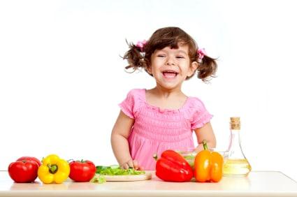 dziecko przy stole z warzywami