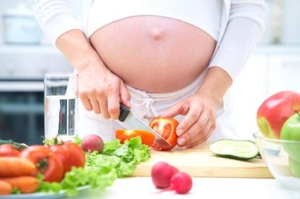 kobieta w ciąży krojąca warzywa